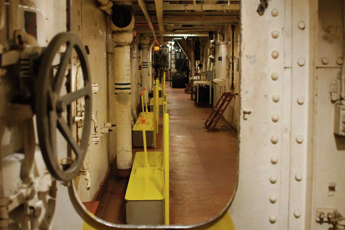 Yellow boiler suspension platforms line the walls of the ammunition passage way on the third deck of the battleship.