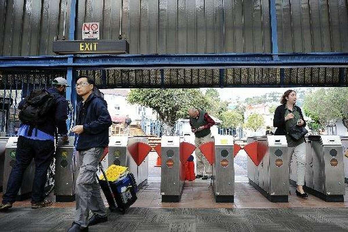 Passengers pass through the turnstiles at the Glen Park BART station in San Francisco, CA, on Thursday, December 18, 2014.