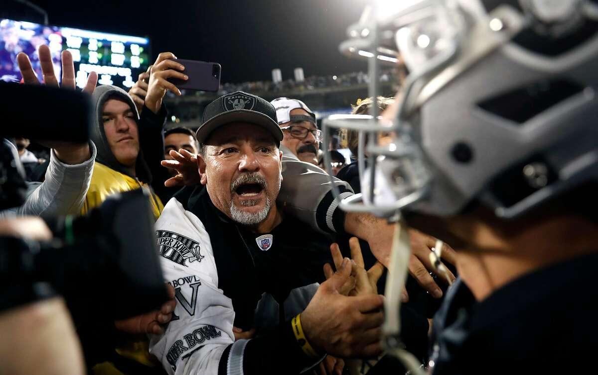 Oakland Raiders' Derek Carr greets fans in The Black Hole after Raiders' 27-14 win over Denver Broncos during NFL game at Oakland Coliseum in Oakland, Calif. on Monday, December 24, 2018.