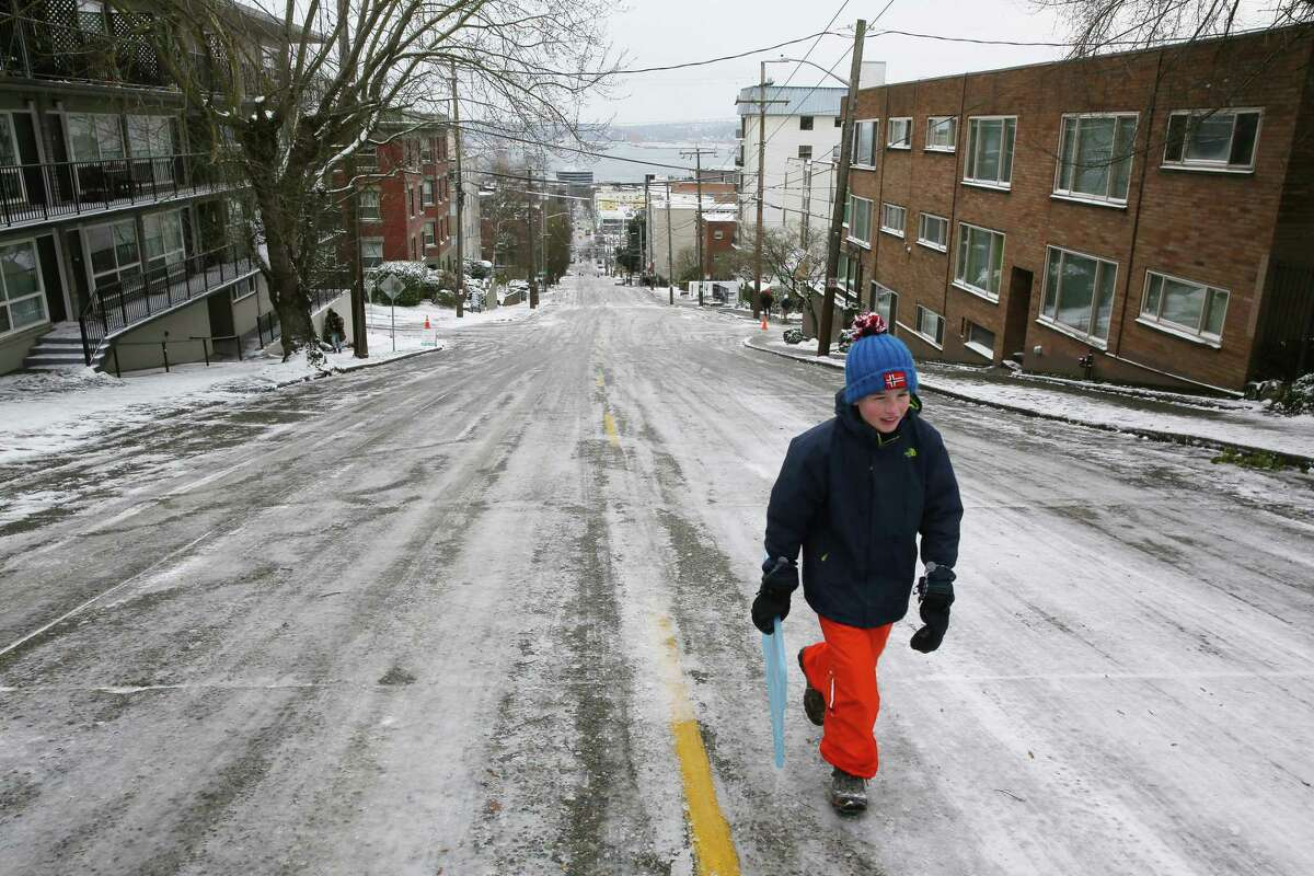 Kids climb a slippery Queen Anne Avenue hill so they can sled back down again, Monday, Feb. 4, 2019.