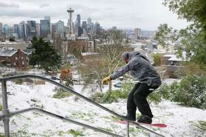 Professional snowboarder Max Dre Djenohan rides a rail at Kerry Park, Monday afternoon, after Seattle saw several inches of snow accumulate over Sunday night and Monday morning, Feb. 4, 2019.