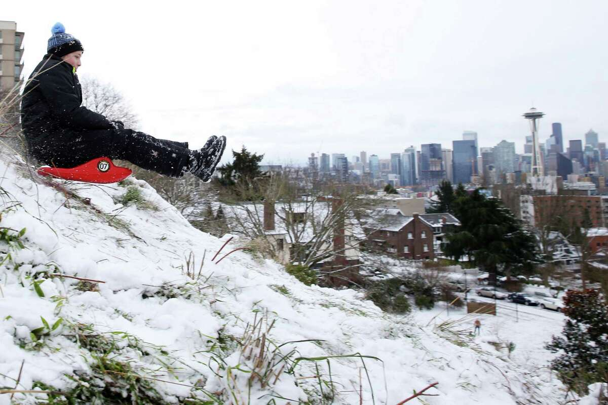 Kids sled at Kerry Park after Seattle saw several inches of snow accumulate over Sunday night and Monday morning, Feb. 4, 2019.