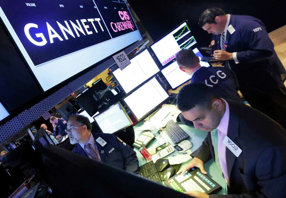 FILE - In this Aug. 5, 2014, file photo, specialist Michael Cacace, foreground right, works at the post that handles Gannett on the floor of the New York Stock Exchange. Gannett, publisher of USA Today, said Monday, Feb. 4, 2019, that its board has unanimously rejected a $1.36 billion buyout offer from a media group with a history of taking over struggling newspapers and slashing jobs. (AP Photo/Richard Drew, File)