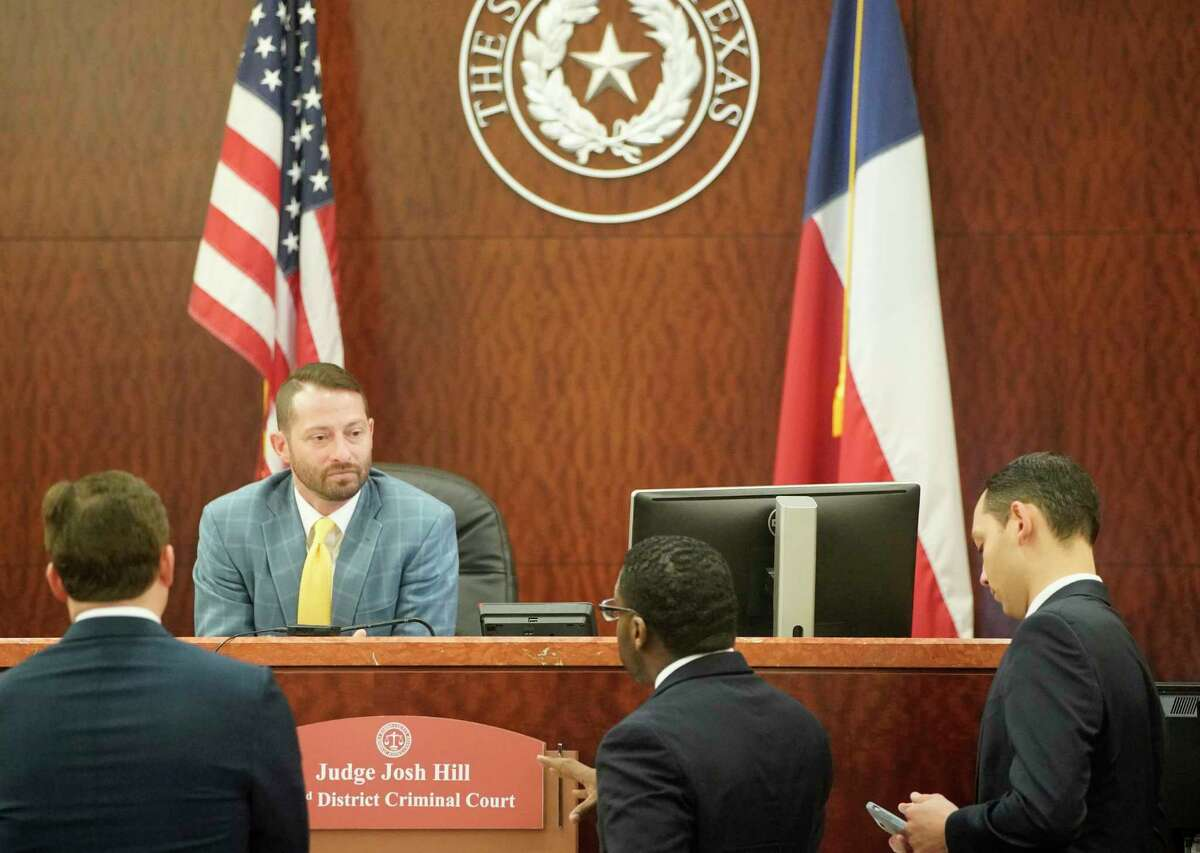 Judge Josh Hill talks with attorneys at the Harris County Criminal Court for the trial of Marco Carrizales, a former Harris County Sheriff's deputy, Monday, Feb. 4, 2019, in Houston. Carrizales is accused of beating a driver so brutally that he broke the man's eye socket and caused serious bodily injury. Sgt. Marco Carrizales was working an extra job in uniform in October 2015, directing traffic for a refinery, when Ismael Garza apparently ran a stop sign, causing Carrizales to give chase.