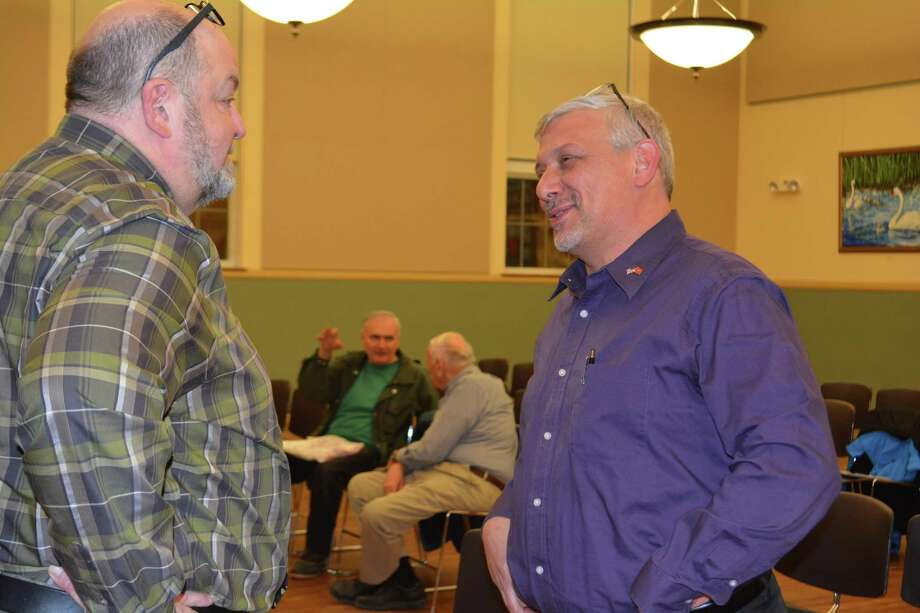 Joel Sekorksi, Torrington's director of services for the elderly, left, talks with newly appointed public works director Ray Drew during Monday's City Council meeting. Photo: Leslie Hutchison / Hearst Connecticut Media /