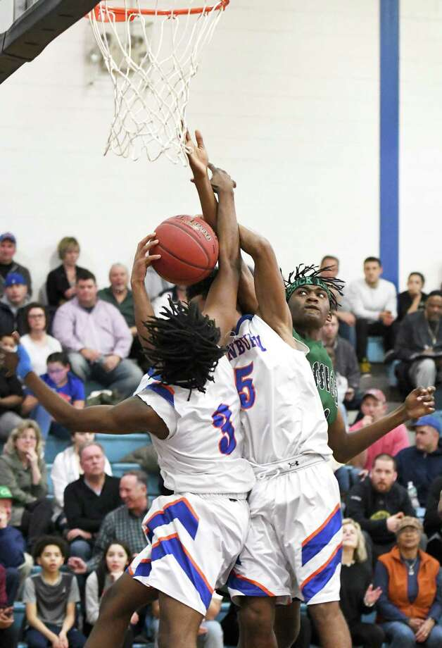 Danbury's Keyon Moore, left, and Javon Hernandez bring down a rebound from Bassick's Isaiah Sullivan, right, during their basketball game at Danbury, Feb. 4, 2019. Photo: Krista Benson / For Hearst Connecticut Media / The News-Times Freelance