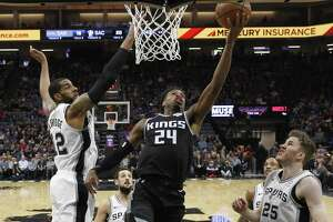 Buddy Hield, center, split the defense of from left, LaMarcus Aldridge, Marco Belinelli, DeMar DeRozan and Jakob Poeltl. DeRozan tied a game-high with 24 points, while Aldridge finished with 22 as the Spurs' five-game win streak ended.