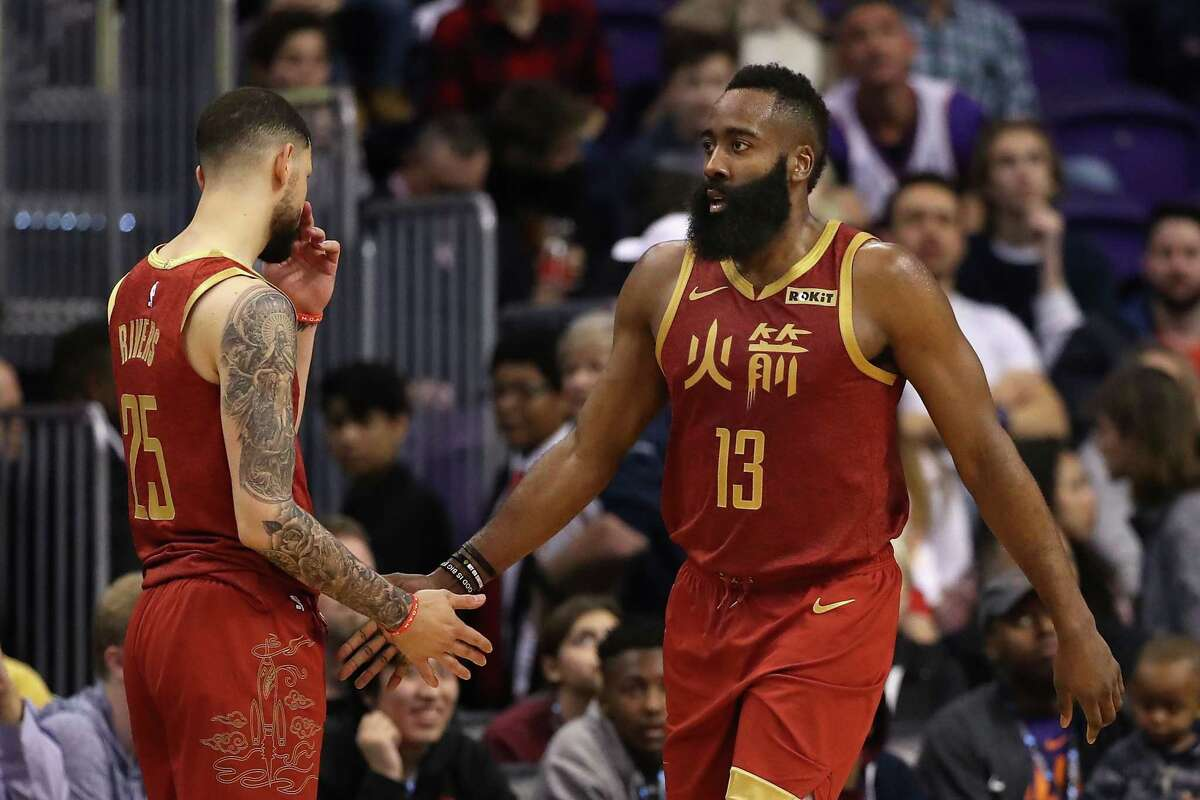 PHOENIX, ARIZONA - FEBRUARY 04: James Harden #13 of the Houston Rockets high fives Austin Rivers #25 after scoring against the Phoenix Suns during the second half of the NBA game at Talking Stick Resort Arena on February 04, 2019 in Phoenix, Arizona. The Rockets defeated the Suns 118-110.