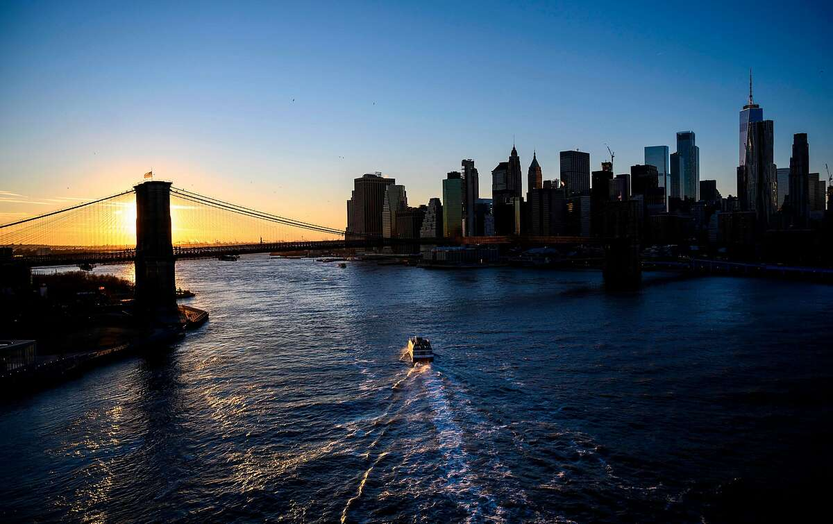This picture taken on January 11, 2019 shows the sun setting behind the iconic Brooklyn Bridge next to the skyline of lower Manhattan in New York City. (Photo by Johannes EISELE / AFP)JOHANNES EISELE/AFP/Getty Images
