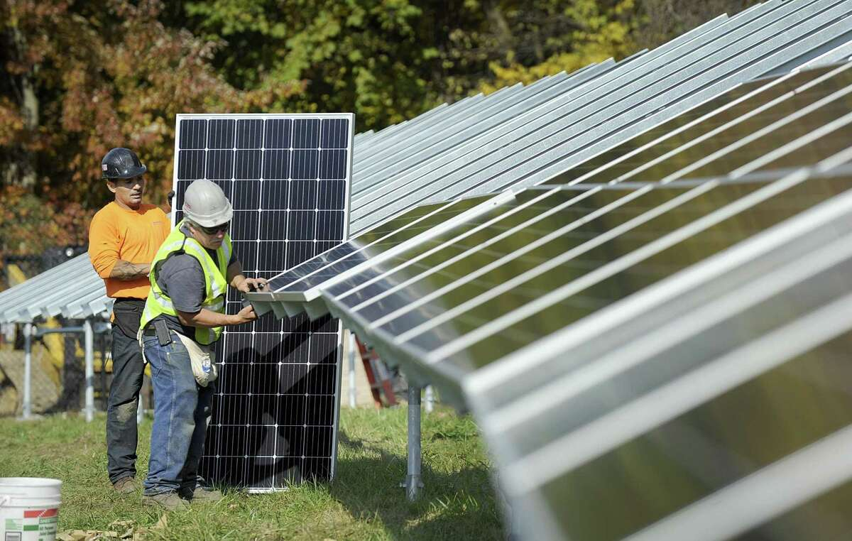 Jose Roman, left, and Bruce Crockett install solar panels at the westside campus of Western Connecticut State University in November. When the project is completed, it is expected to save the university at least $10,000 in energy costs in the first year and $580,000 over 25 years.