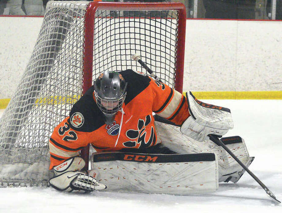 Edwardsville goalie Mason Young covers up the puck during the second period of Saturday's game against Marquette at the Brentwood Ice Rink. Photo: Scott Marion | For The Telegraph