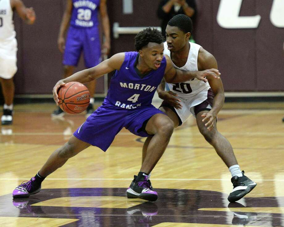 LJ Cryer (4) of Morton Ranch is guarded by Chris Ngene (20) of Cinco Ranch during the second half of a high school basketball game between the Cinco Ranch Cougars and the Morton Ranch Mavericks on Tuesday. Photo: Craig Moseley, Houston Chronicle / Staff Photographer / ©2019 Houston Chronicle