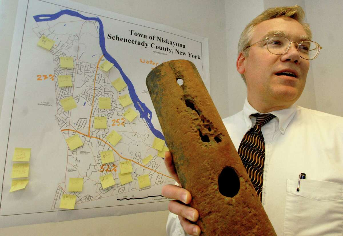 Times Union staff photo by Cindy Schultz Richard Pollock, supervisor of water, sewer and engineering, holds a corroded water pipe by a map that documents water breaks from 2004 through 2005 on Wednesday, April 19, 2006, at Niskayuna Town Hall in Niskayuna, N.Y.