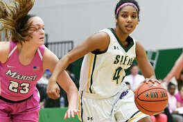 Siena guard Sabrina Piper (42) moves the ball past Marist guard Rebekah Hand (23) during the first half of an NCAA women's college basketball game Friday, Feb. 1, 2019, in Loudonville, N.Y.