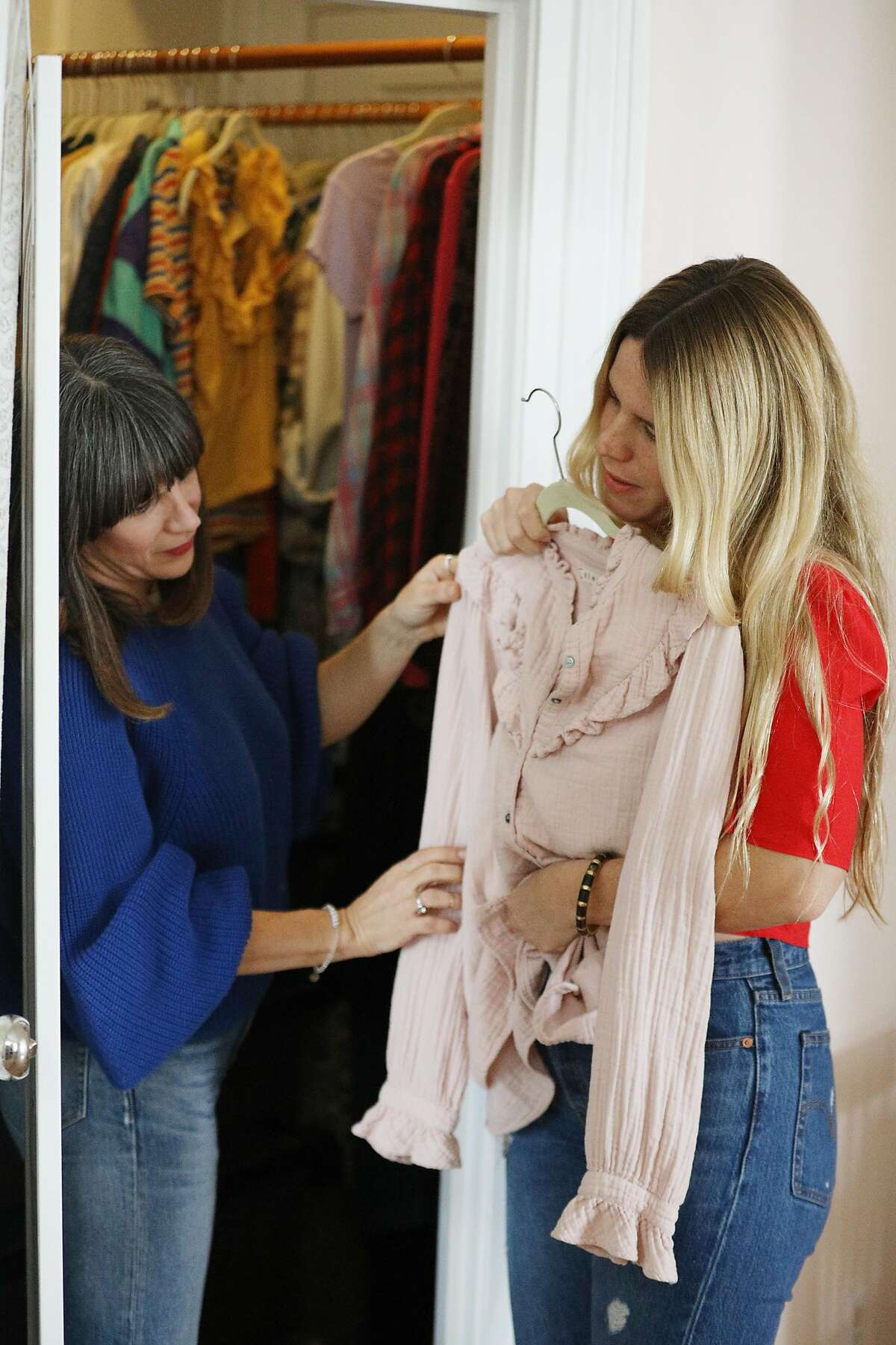 Mira Pickett (l to r), owner Mira Mira The Edit, and client Joanna Riedl discuss a top from Riedl's closet during a a closet and style consultation on Monday, February 4, 2019 in San Francisco, Calif.