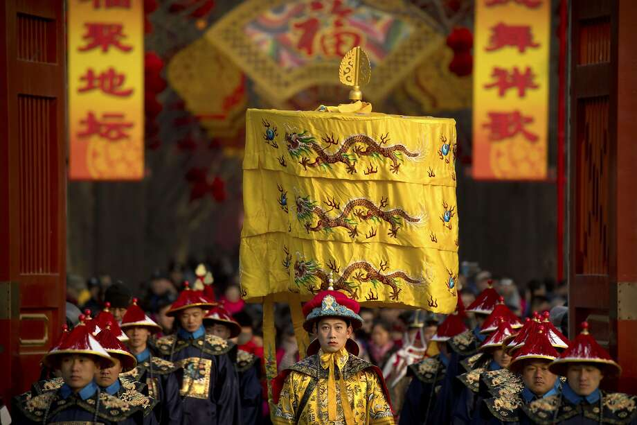 A performer dressed as an emperor (center) participates in a Qing Dynasty ceremony in which emperors prayed for a good harvest and good fortune at a temple in Beijing on the first day of the Lunar New Year. Photo: Mark Schiefelbein / Associated Press
