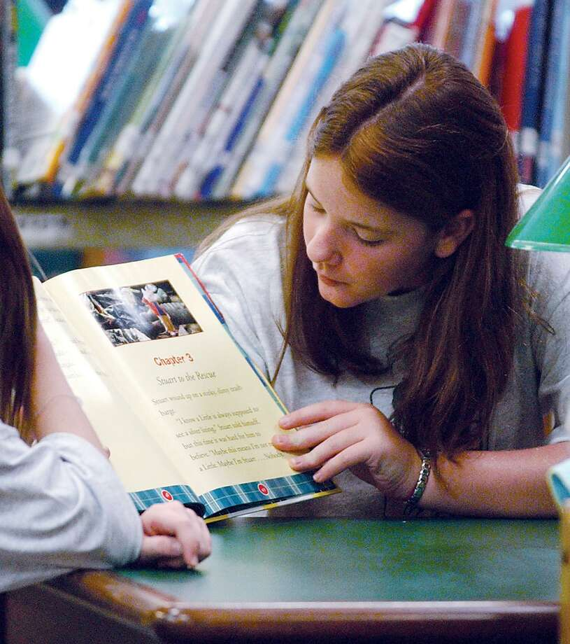 A young lady reads to her book buddies at the Durham Public Library in this archive shot. Photo: File Photo