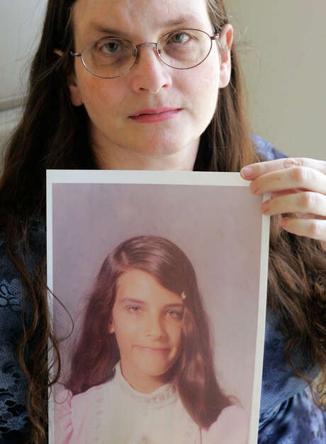 In this 2007 file photo, Debbie Vasquez holds a photo of herself at age 14, when she says she was first molested by the pastor of her church in Sanger, about one hour north of Dallas. (Donna McWilliam/Associated Press)