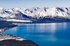 Aerial view of Lake Tahoe on a sunny winter day in California. Sierra mountains covered in snow are visible in the background.