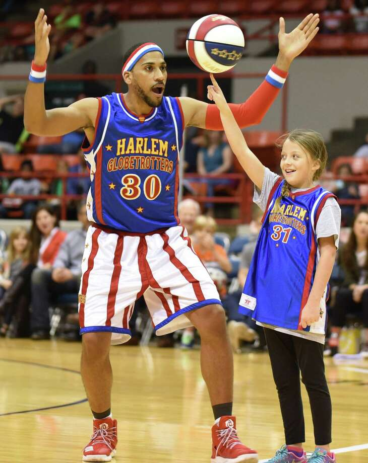 Zeus McClurkin, seen here with a fan, will be among the Harlem Globetrotters at Webster Bank Arena in Bridgeport on Friday, Feb. 15, at Hartford's XL Center on Saturday, Feb. 16, and back at Webster Bank Arena on Monday, Feb. 18. Photo: Brett Meister / Contributed Photo