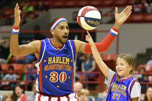 Zeus McClurkin, seen here with a fan, will be among the Harlem Globetrotters at Webster Bank Arena in Bridgeport on Friday, Feb. 15, at Hartford's XL Center on Saturday, Feb. 16, and back at Webster Bank Arena on Monday, Feb. 18.