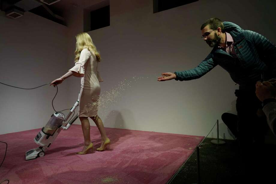 "A spectator tosses crumbs for an Ivanka Trump lookalike to vacuum at Jennifer Rubell's art exhibit ""Ivanka Vacuuming 2019"" on Tuesday, Feb. 5, 2019, at Flashpoint Gallery in Washington. The art piece titled ""Ivanka Vacuuming,"" runs through Feb. 17 at the Flashpoint Gallery. Photo: Sait Serkan Gurbuz, AP / Copyright 2019 The Associated Press"
