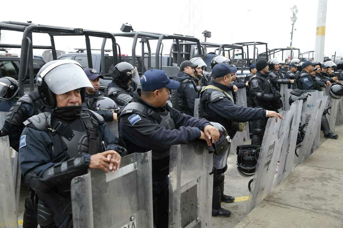 Mexican Federal Police wear riot gear as they guard the outside of a migrant shelter for Central American immigrants in Piedras Negras, Mexico, Tuesday, Feb. 5, 2019. The group numbering around 1,700 is at a state run shelter across the Rio Grande from Eagle Pass, Texas. The immigrants arrived on Monday and most are seeking asylum in the U.S. Immigrants with humanitarian visas issued by Mexico were allowed to leave the shelter.