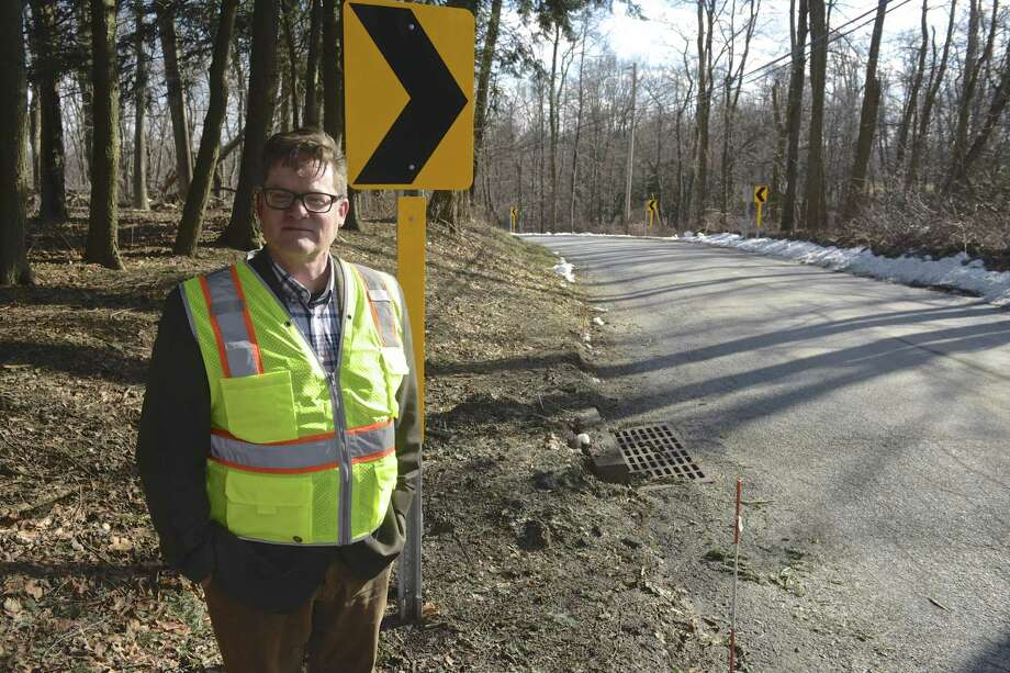 Sherman First Selectman Don Lowe stands with new curve signs that were installed on Wakeman Hill Road on Jan. 25 in Sherman. An abundance of curve warning signs were installed as part of a federal grant. Photo: H John Voorhees III / Hearst Connecticut Media / The News-Times
