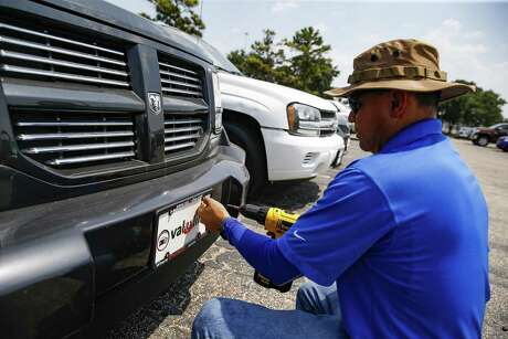 Sterling McCall Toyota porter Raul Villalta puts a Val-U-Line license plate on a car Thursday July 26, 2018 in Houston. The Group 1 Auto dealership posted record sales, driven in part by strong used car sales. (Michael Ciaglo / Houston Chronicle)