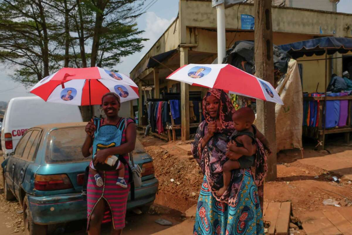 Women in Yaounde, Cameroon, carry umbrellas they received as campaign handouts featuring Paul Biya, president since 1982.