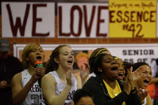 A sign made in memory of Essence Glover, a teammate who died at the beginning of the school year, is visble behind members of the Lee girls basketball team as they celebrate a basket scored against Wolfforth Frenship, Feb. 5, 2019, at Lee High School. James Durbin/Reporter-Telegram
