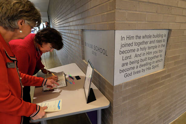 Bynum School's Janna McGarrity, foreground, and Nancy Woodman, background, former member of the Bynum School's building capital campaign committee, look through a Bible that will be placed inside the cornerstone, during a ribboncutting and dedication ceremony for the Bynum School Feb. 5, 2019. James Durbin/Reporter-Telegram