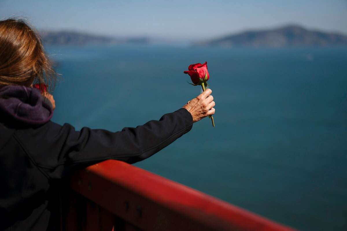 Kymberlyrenee Gamboa and her husband, Manuel Gamboa take a moment before tossing over a rose at the Golden Gate Bridge in San Francisco, Calif., on Thursday, Sept. 20, 2018. The Gamboa's waited to throw the rose till 11:45 a.m the moment that Kyle Gamboa had jumped off the bridge to his death.