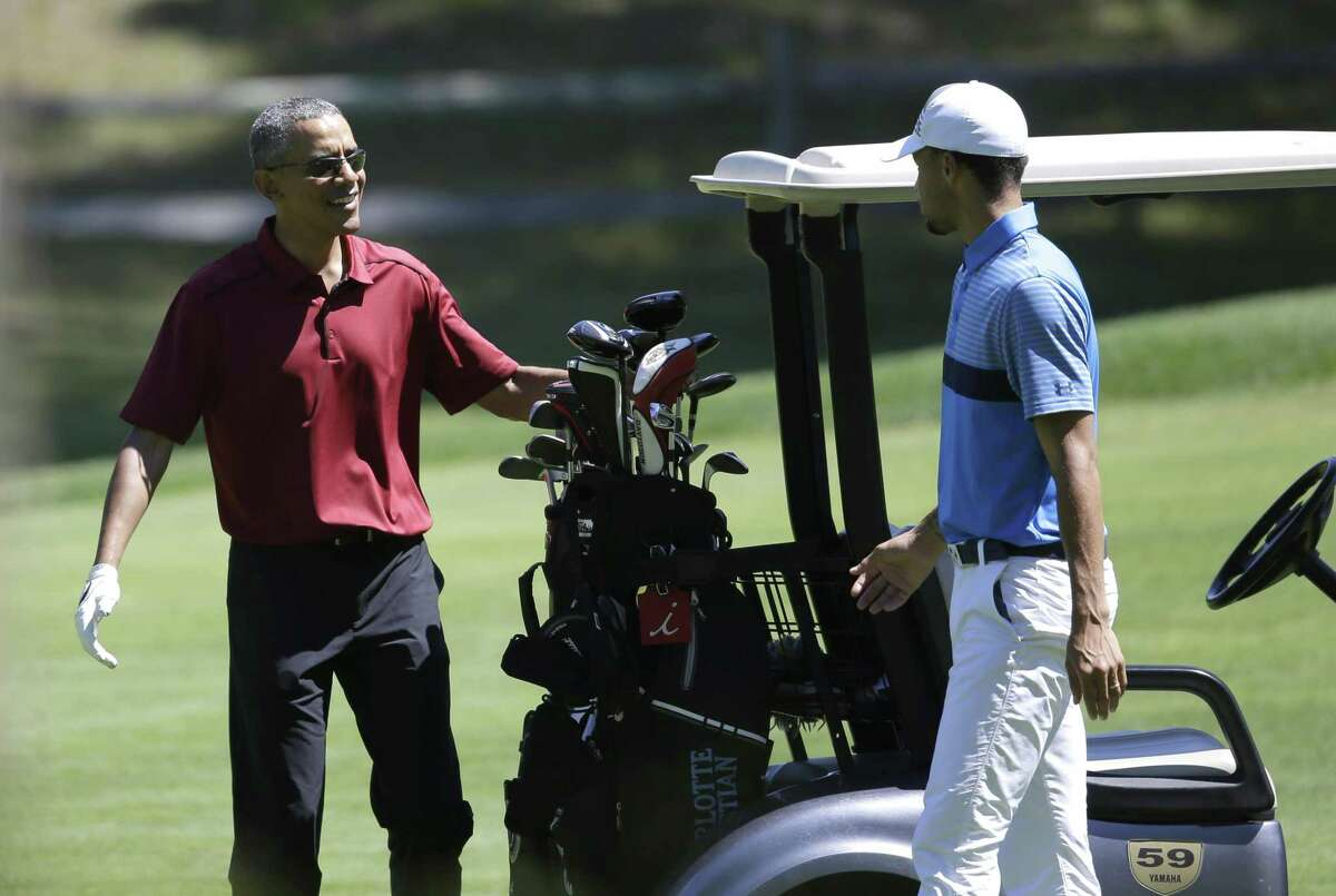 President Barack Obama, left, speaks with NBA basketball player Stephen Curry, right, while golfing Friday, Aug. 14, 2015, at Farm Neck Golf Club, in Oak Bluffs, Mass., on the island of Martha's Vineyard. The president, first lady Michelle Obama, and daughter Sasha are vacationing on the island.
