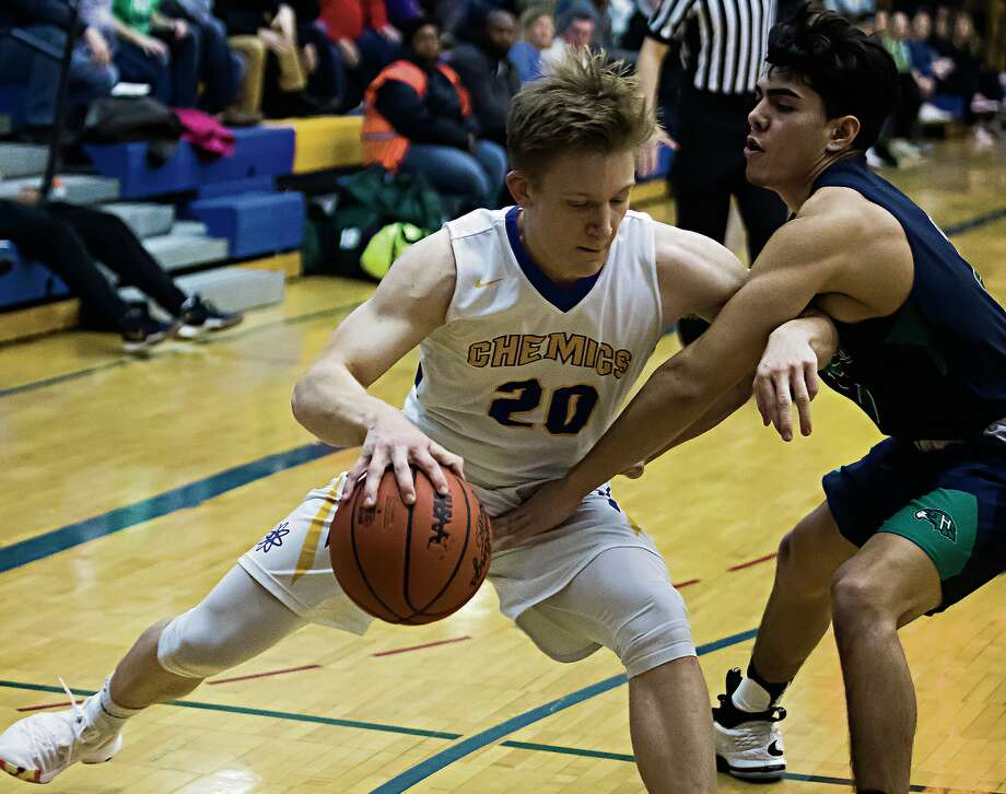 Midland High's John White (left) tries to stave off Saginaw Heritage's Jayce Garcia during Tuesday's game at the Chemics' gym. Photo: Katykildee/kildee@mdn.net