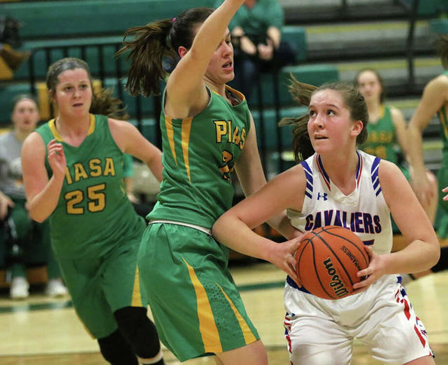 Carlinville's Sarah DeNeve (right) looks to the basket while Southwestern's Bailey Weible defends and the Birds' Molly Novack (25) retreats the the basket in the Southwestern Class 2A Regional on Tuesday night in Piasa. Photo: Greg Shashack | The Telegraph
