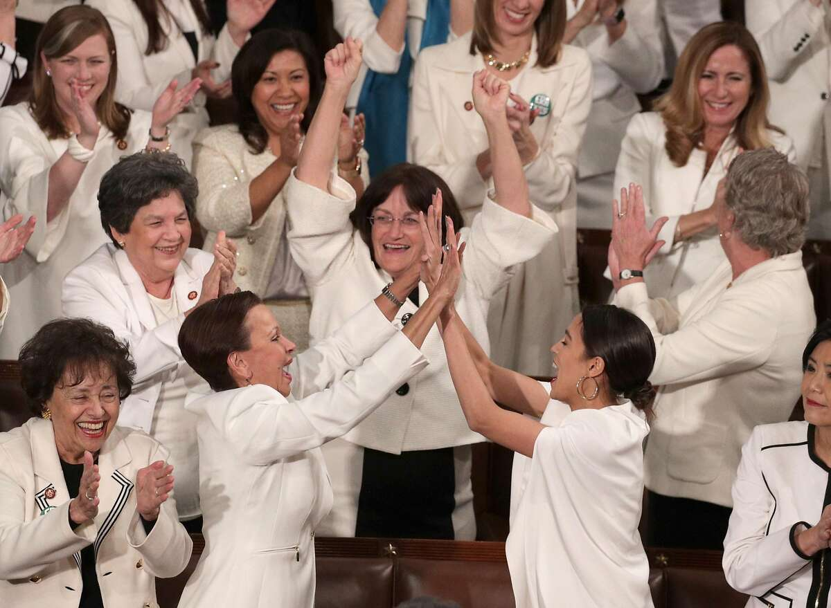 Rep. Alexandria Ocasio-Cortez (D-NY) and other female lawmakers cheer during President Donald Trump's State of the Union address in the chamber of the U.S. House of Representatives at the U.S. Capitol Building on February 5, 2019 in Washington, DC. A group of female Democratic lawmakers chose to wear white to the speech in solidarity with women and a nod to the suffragette movement.