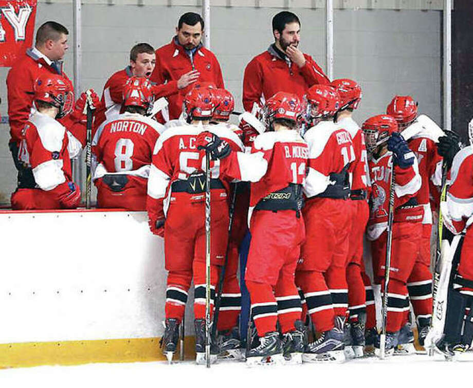 The Alton High hockey team will open a Class 1A semifinal series against Bethalto Thursday night in Granite City. The Redbirds are shown between periods during a 2017 game. Current AHS head coach Aaron Kestler is far left. Photo: Billly Hurst File | For The Telegraph