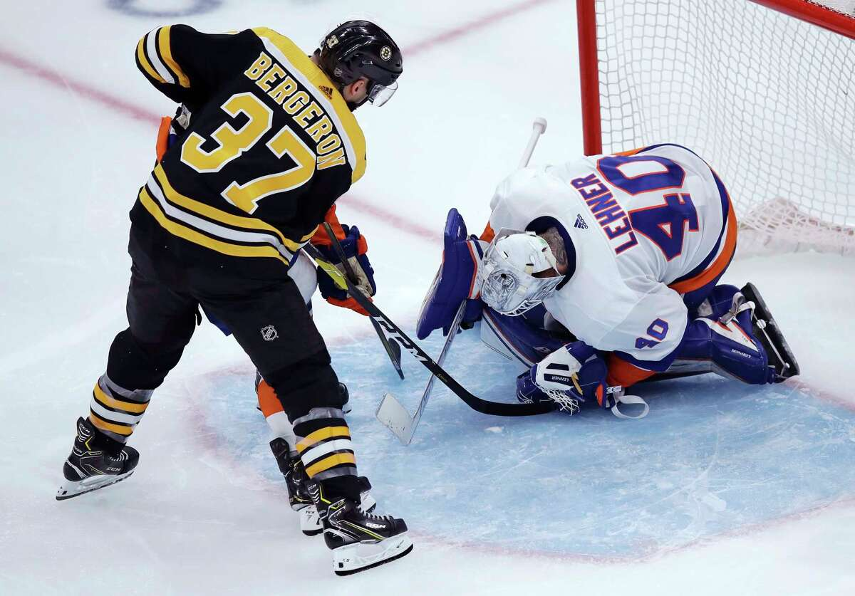 New York Islanders goaltender Robin Lehner (40) drops to make a save against Boston Bruins center Patrice Bergeron (37) during third period of an NHL hockey game in Boston, Tuesday, Feb. 5, 2019. The Bruins defeated the Islanders 3-1. (AP Photo/Charles Krupa)