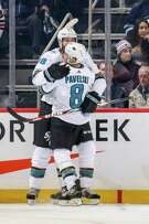 Joe Pavelski #8 and Brent Burns #88 of the San Jose Sharks celebrate after scoring the overtime winning goal against the Winnipeg Jets at the Bell MTS Place on February 5, 2019 in Winnipeg, Manitoba, Canada.