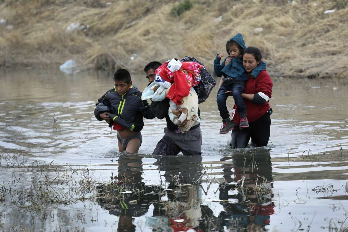 Central American immigrants wade across the Rio Grande from Mexico into the United States on February 01, 2019 in El Paso, Texas.