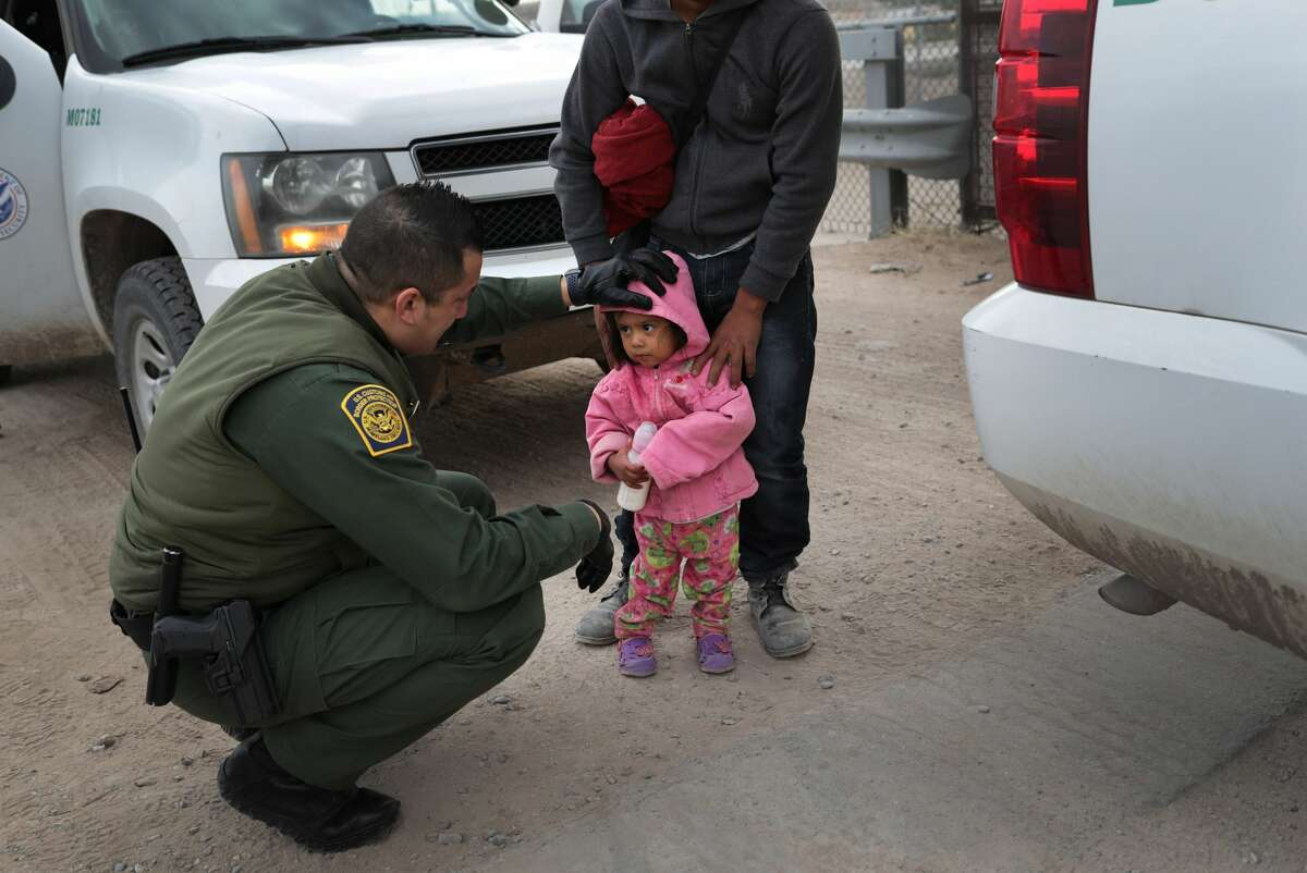 A U.S. Border Patrol agent speaks with Central American immigrants after they crossed the border from Mexico on February 01, 2019 in El Paso, Texas. Agents took the migrants, who were seeking asylum in the United States, into custody.