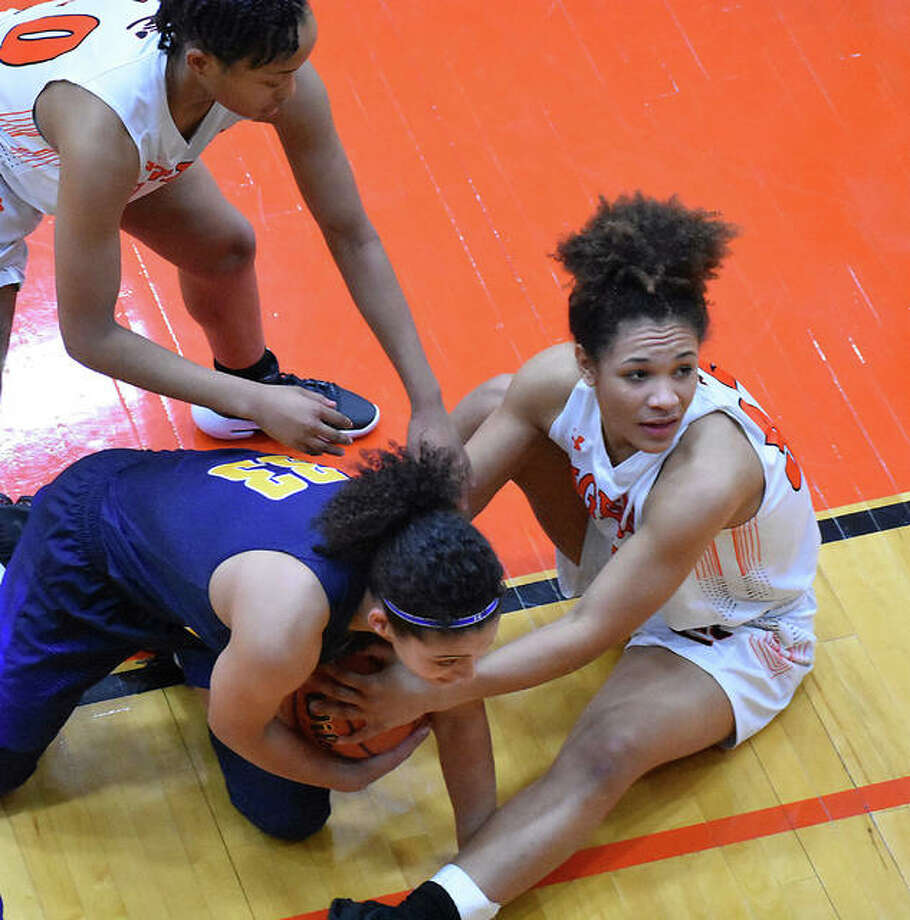Edwardsville's Maria Smith (right) looks to the ref for a call after a scramble for a loose ball during a Southwestern Conference girls basketball game Tuesday night at Lucco-Jackson Gym in Edwardsville. Photo: Matt Kamp / Hearst Illinois