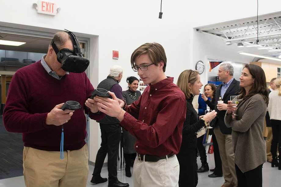 George Chieffi, a King School junior from Darien, assists a guest with the Virtual Reality equipment in King School's Innovation Lab in Stamford, Conn. on Jan. 30, 2019. Photo: Contributed Photo / Contributed Photo / Stamford Advocate contributed