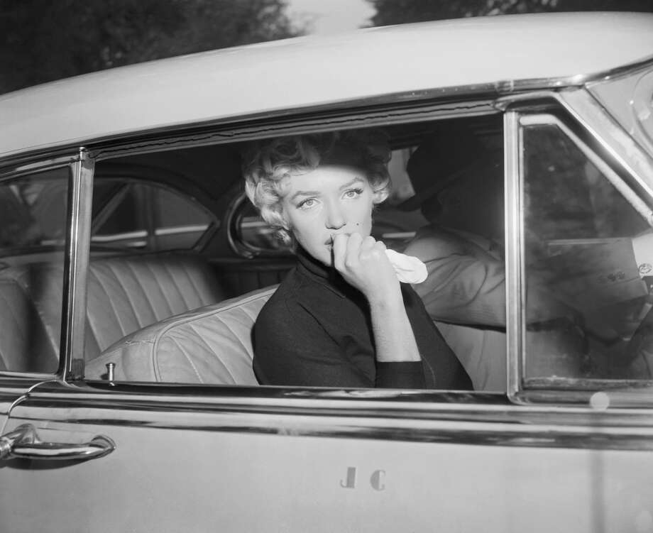 """Marilyn Monroe leaves the home she briefly shared with Joe DiMaggio in a car driven by her attorney, Jerry Giesler. Monroe had just announced her intent to divorce DiMaggio on grounds of """"mental cruelty."""" Photo: Bettmann/Bettmann Archive"""