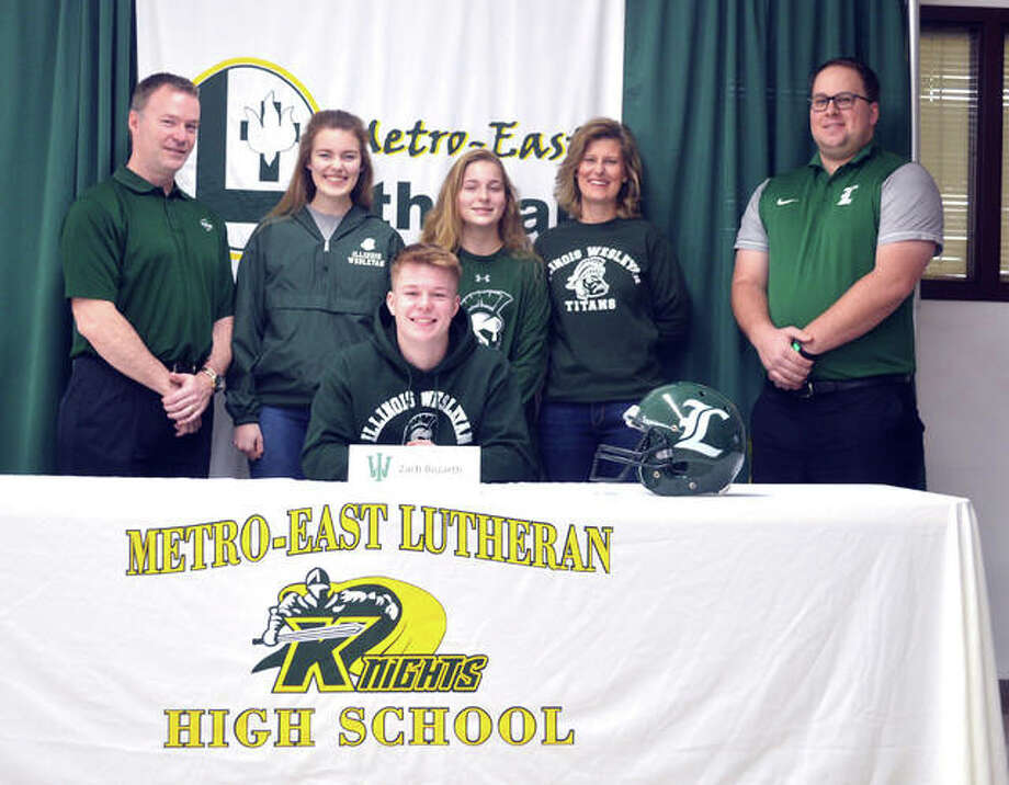 Metro-East Lutheran senior Zach Bozarth, seated, signed to play football at Illinois Wesleyan University. He is joined by his family and MELHS coach Micah Pomerenke. Photo: Scott Marion/Intelligencer