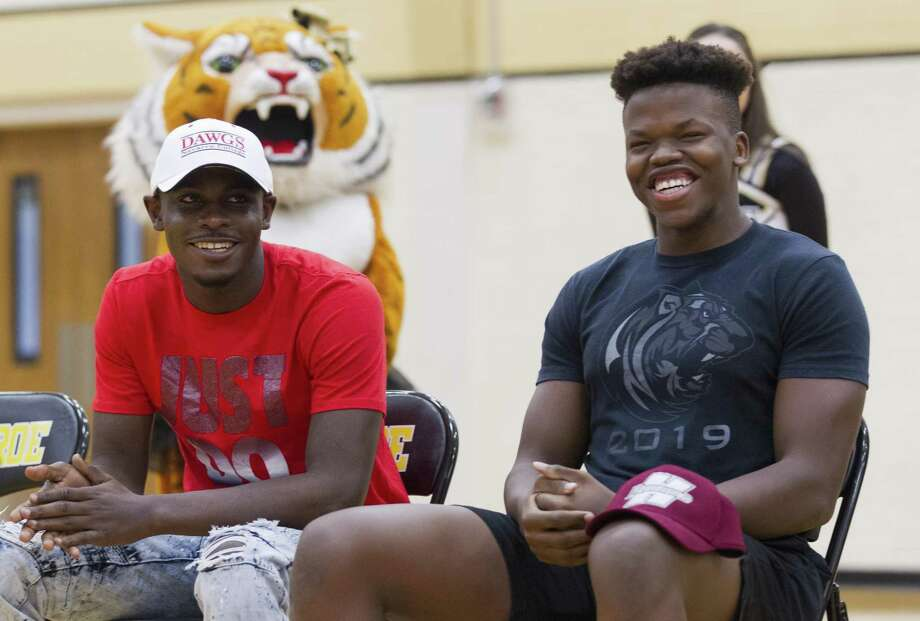 "Dylan Ndambuki, right, shares a laugh next to teammate Davian ""Coco"" Sneed during a National Signing Day ceremony at Conroe High School, Wednesday, Feb 6, 2019, in Conroe. Ndambuki signed to play football for Henderson State University, while Sneed signed with Navarro College. Photo: Jason Fochtman, Houston Chronicle / Staff Photographer / © 2019 Houston Chronicle"