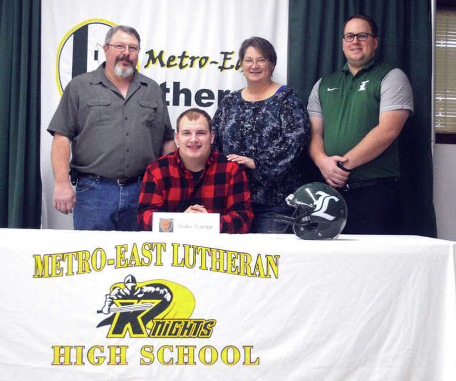 Metro-East Lutheran senior Drake Trampe, seated, signed to play football at Greenville University. He is joined by his family and MELHS coach Micah Pomerenke. Photo: Scott Marion/Intelligencer