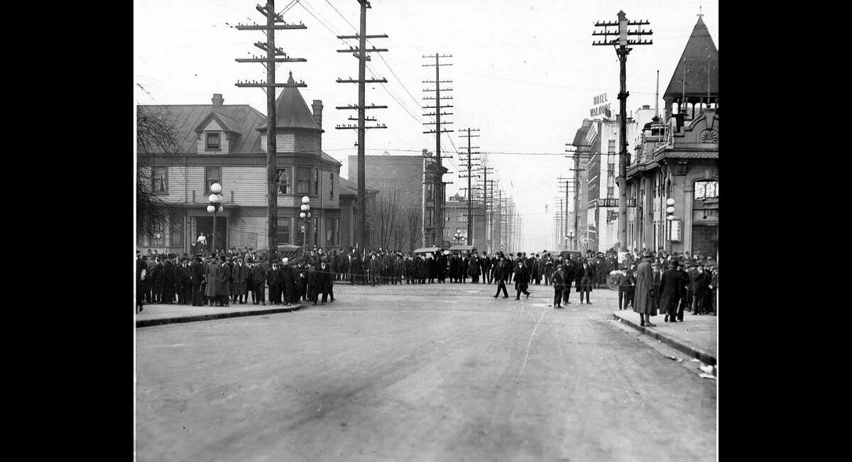 """""""One of the few crowd scene photographs from the strike. The location is Seventh Avenue and Union, one block from the Labor Temple strike headquarters, but even closer to the offices of the Star. This photo may show strikers, but it is more likely that people were awaiting the first newspaper to be published during the strike late on day 2. (Friedheim, R., & Gregory, James N. (2018). The Seattle general strike (Centennial ed.). Seattle: University of Washington Press.)."""" -UW Special Collections"""
