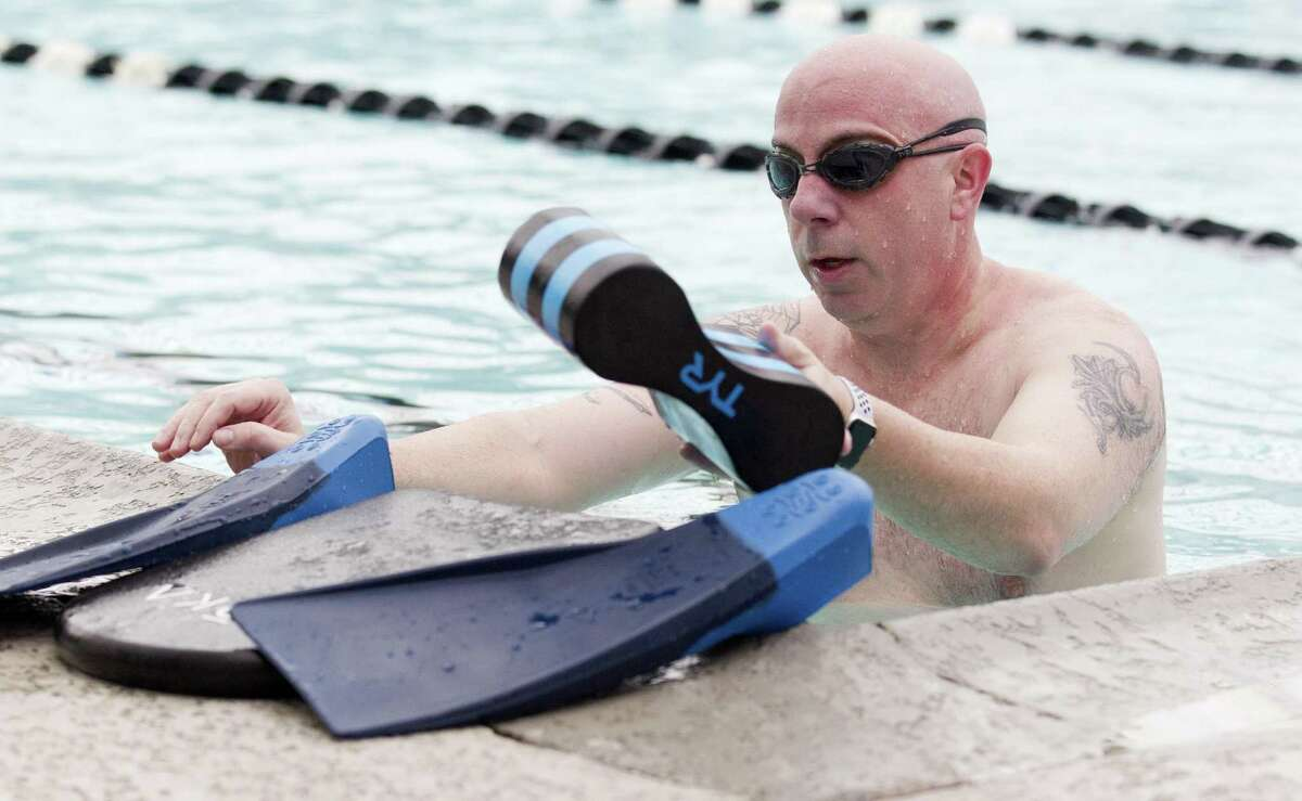 John Anthony Brown, board member with The Woodlands Township, puts up equipment after training for the swimming portion of the upcoming Ironman competition at Shadowbend YMCA, Wednesday, Jan 30, 2019, in The Woodlands.